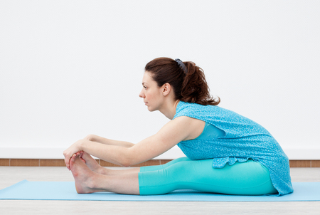 Yoga. Fitness. Stretching. Young woman is doing stretching  on the mat, touching the feet,  white background Archivio Fotografico