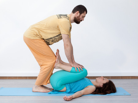 somatic: Pair exercises. Massage. Man performing thai massage, srtetching womans legs, presses on her ankles