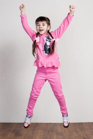 hooray: Children. Expressions. Hooray.  A cute little girl in pink clothes is jumping raising the hands up