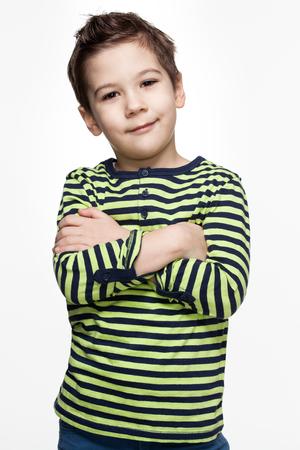 niÑos contentos: Niños. Emociones. Retrato de un niño pequeño contenta con las manos cruzadas, fondo blanco Foto de archivo