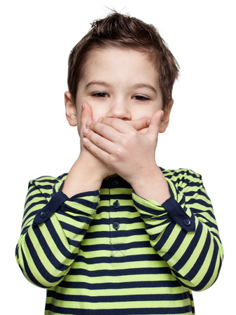 shutting: Children. Expressions. Close up portrait of a  little boy in a striped shirt, he is shutting down the mouth by the hands , white background Stock Photo