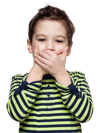 guardar silencio: Niños. Expresiones. Cerca de retrato de un niño pequeño en una camisa a rayas, que está cerrando la boca por las manos, fondo blanco Foto de archivo