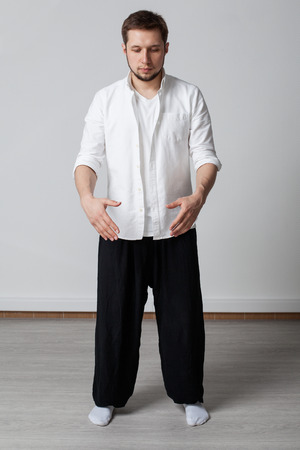 taichi: Practice. Young man in white shirt and black pants performing tai chi exercise Stock Photo