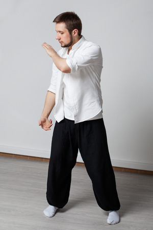 qigong: Practice. Qigong. Young man in white shirt and black pants performing tai chi exercise Stock Photo