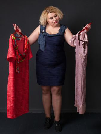 finery: Choise. Mature blonde woman is choosing one of two dresses Stock Photo