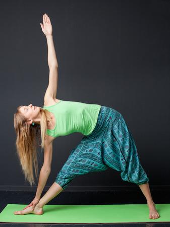 trikonasana: Utthita Trikonasana. Yong woman in green shirt and blue pants performing yoga asana