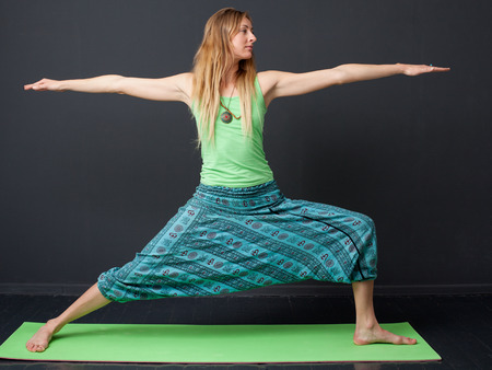 virabhadrasana: Yoga. Virabhadrasana. Young blonde woman performing  warrior Pose, gray background