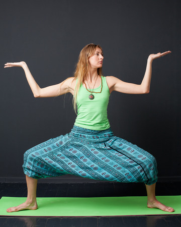 yoga pants: Rudrasana.  Yong woman in green shirt and blue pants staying in yoga pose