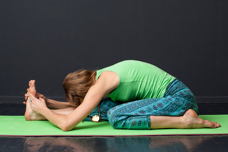 padma: Ardha baddha padma paschimottanasana. A young blonde woman performing yoga asana, gray background