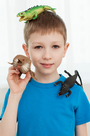 upgrowth: Close up portrait of a boy playing with dinosaur toys Stock Photo