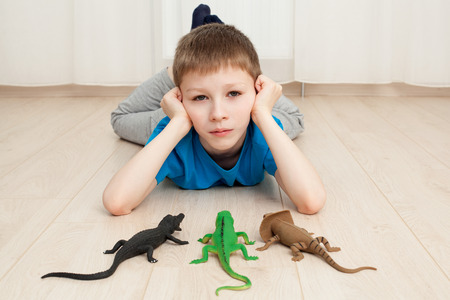 upgrowth: Close up a lonely boy laying on the floor with some toys, looking sad Stock Photo