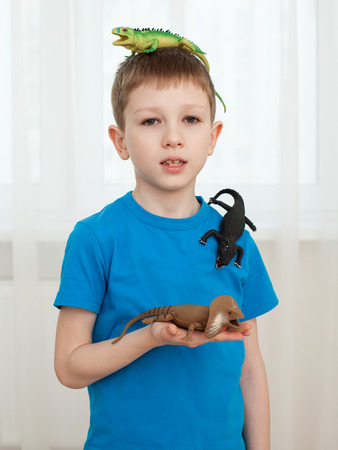 upgrowth: Portrait of a boy playing with dinosaur toys, holding a lizard on the head