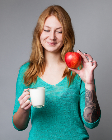 carroty: Portrait of a young ginger lady in turquoise blouse with red apple in one hand and a cup of milk in the other hand, grey background Stock Photo