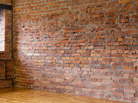 unfurnished: Room unfurnished. Interior with red brick walls and wooden flooring of boards. Light falls from the window. Stock Photo