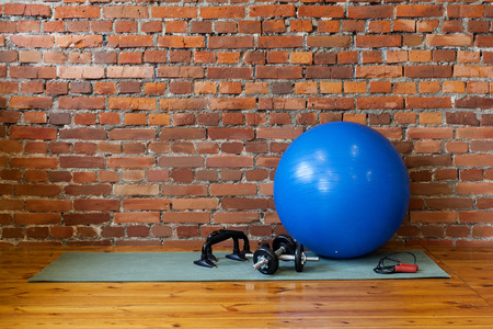 fitball: Place for fitness and exercise. The mat, fitball, rope, dumbbells and stand push-ups lie on the floor in the gym.