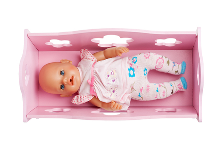 baby isolated: A baby doll laying in the pink crib isolated on white background