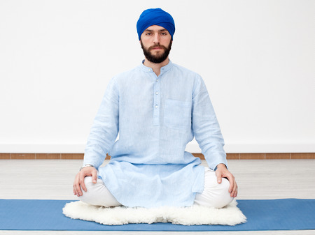 kundalini meditation: Meditation. Portrait of a young bearded yogi man in a turban, hands laying on the knees, sitting on the sheep skin in a lotus pose