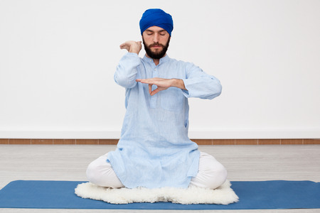kundalini: Meditation. Young yogi man in a turban sitting on the mat doing mudra, front view Stock Photo