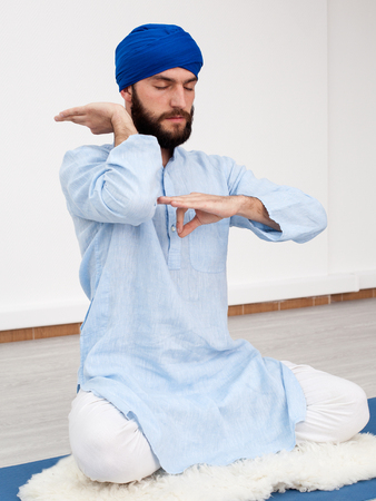 kundalini: Meditation. Young yogi man in a turban sitting on the mat doing mudra, half turned view Stock Photo