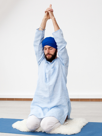kundalini: Meditation. Young yogi doing extension, hands up, eyes are closed, sitting on the mat