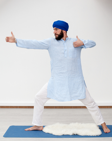 kundalini: Yoga. Young bearded man in a turban performing archer pose on the mat