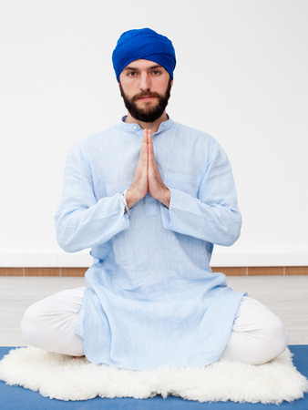 kundalini: Meditation. Portrait of a young bearded man in a turban with hands folded on the chest level, sitting on the sheep skin in a meditative pose