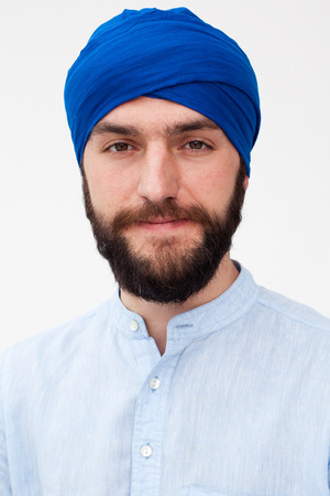 kundalini: Close up portrait of a young bearded man in a turban smiling, white background Stock Photo