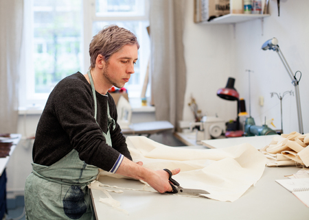 snipping: Workshop. Young man tailor snipping the cloth Stock Photo