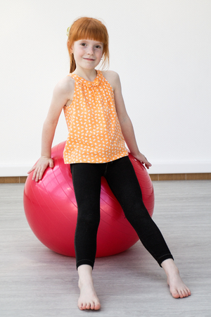 Children's lifestyle and fitness. Little girl practicing on fitball at the gym. Stockfoto
