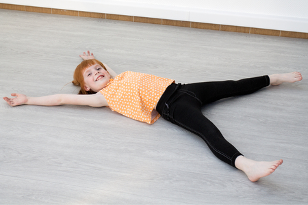 Little redheaded girl laying on the floor, looking into the camera and smiling Stok Fotoğraf - 58154013