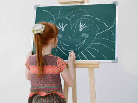 rowth: The little red-haired girl draws on a school board. The image on a white background.