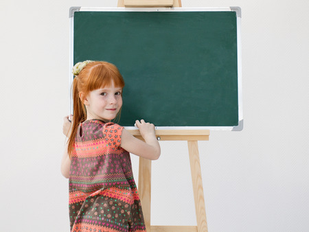 rowth: The little red-haired girl with freckles standing around  board without inscriptions. The image on a white background.