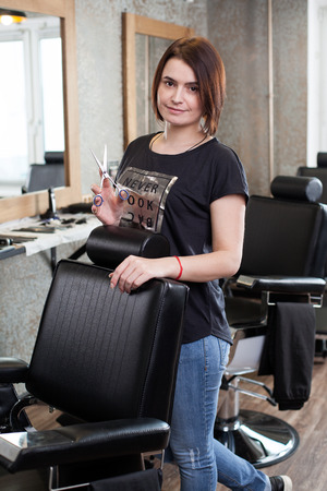 barber scissors: Portrait of a young woman- barber with scissors at work in the barbershop