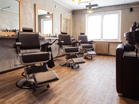 Hairdressing salon. Interior of a barbershop, armchairs and mirrors