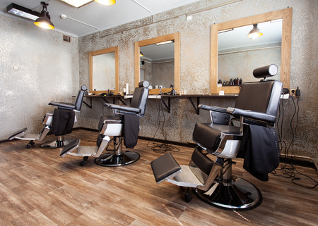 Hairdressing salon.Three workplaces for barbers, armchairs and mirrors Stock Photo