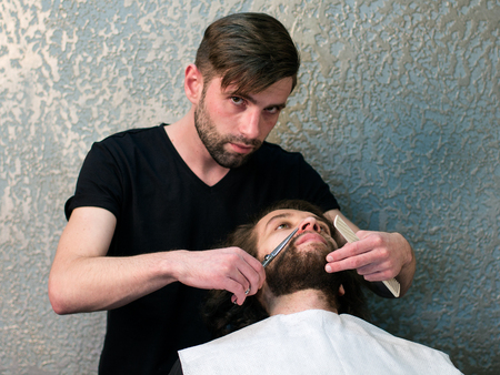 hairdressing scissors: Hairdressing salon. A barber is shaving mans beard with the scissors and the comb Stock Photo