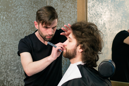 straight razor: Hairdressing salon. A barber is shaving mans beard with the straight razor Stock Photo