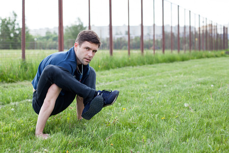 outdoor exercise: Outdoor yoga workout. Young man doing an exercise in the city park Stock Photo
