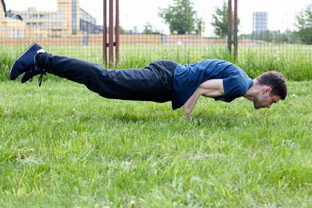 planck: Outdoor yoga workout. Young man doing an exercise in the city park, peacock pose Stock Photo