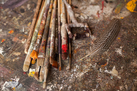 art materials: Art materials. Different brushes and a quill on gray sloppy surface Stock Photo