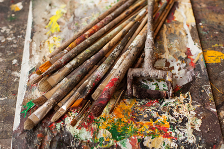 bedraggled: Art materials. Different bedraggled used brushes on gray sloppy surface Stock Photo