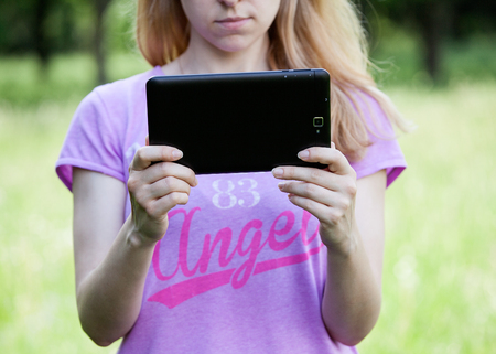 scratchpad: Young blonde woman holding a tablet outdoors, looking at the screen, green background Stock Photo