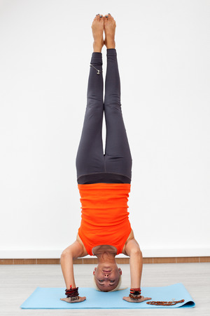 handstand: Yoga workout. Blonde woman doing handstand on the mat indoors, front view Stock Photo