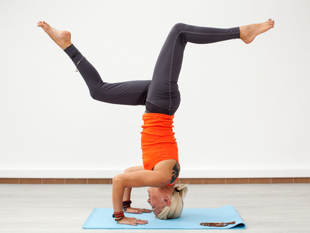 handstand: Yoga workout. Blonde woman doing handstand on the mat indoors, side view