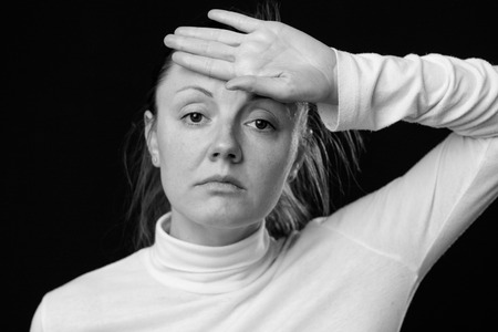 hand on forehead: Headache. Close up portrait of a sad woman, holding the hand on the forehead, looking down, isolated on white background, black and white
