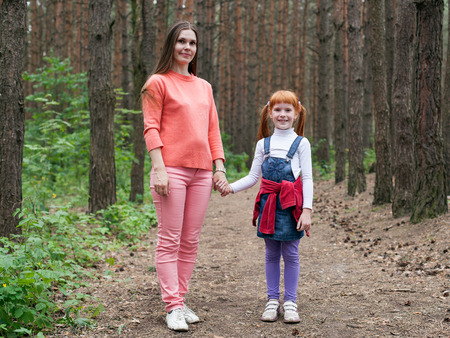 full height: Mother and daughter holding hands in a forest, portrait of full height Stock Photo