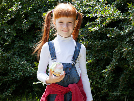 broadly: The little red-haired girl in blue jeans with freckles holds a cake with cream and smiling broadly, greenery background Stock Photo