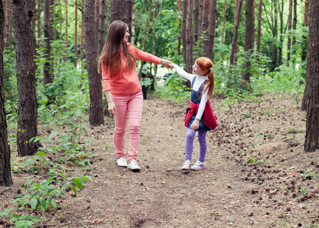 holding hands while walking: Happy mother and daughter looking at each other holding hands while walking on a forest path