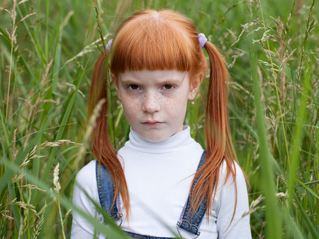 Little sad girl with a puffed cheeks looking reproachfully at the camera. Portrait close up on a background of green grass. Stock Photo