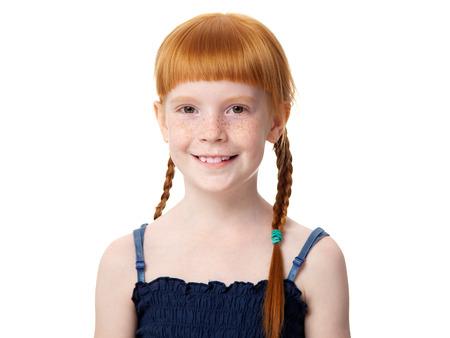Portrait of a beautiful redhead joyful little girl in a blue dress on a white background